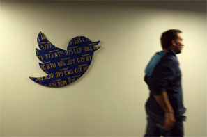 Image: An employee walks past a Twitter logo made from Californian license plates at the company's headquarters in San Francisco. Photograph: Robert Galbraith/Reuters