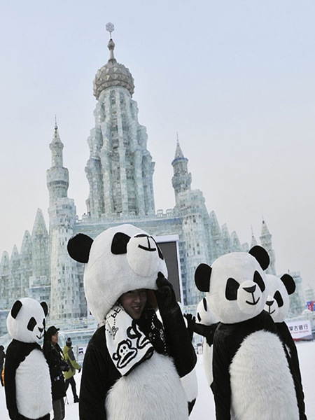 Employees wearing panda costumes stand in front of giant ice sculptures during the Harbin International Ice