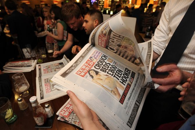 Men read the last edition of News of The World tabloid.