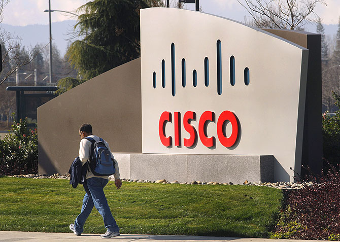 A pedestrian walks past the Cisco logo at the technology company's campus in San Jose.