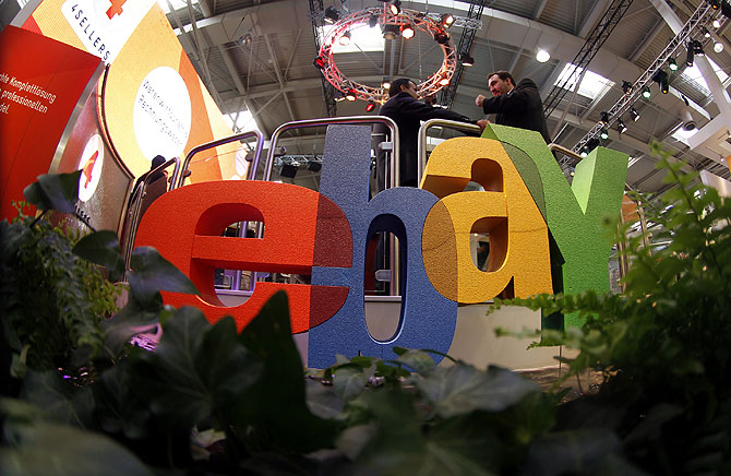 Visitors chat next to the Ebay logo at the CeBIT computer fair in Hanover.