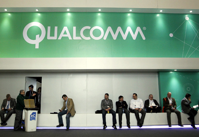 People sit next a Qualcomm stand at the Mobile World Congress at Barcelona.