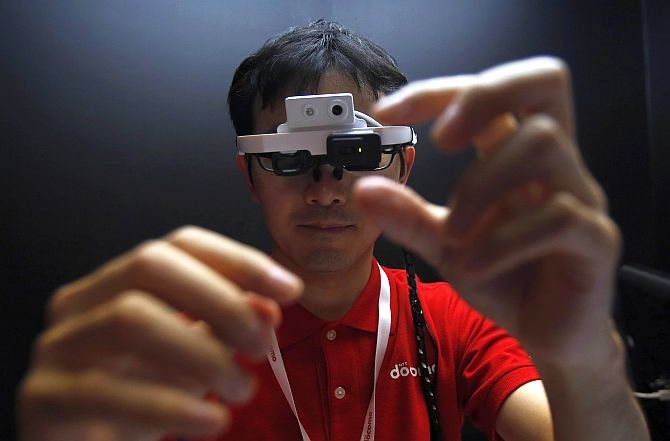 A staff member of NTT DoCoMo Inc wears a head-mounted intelligent glass, which enables the display of touchable augmented reality.