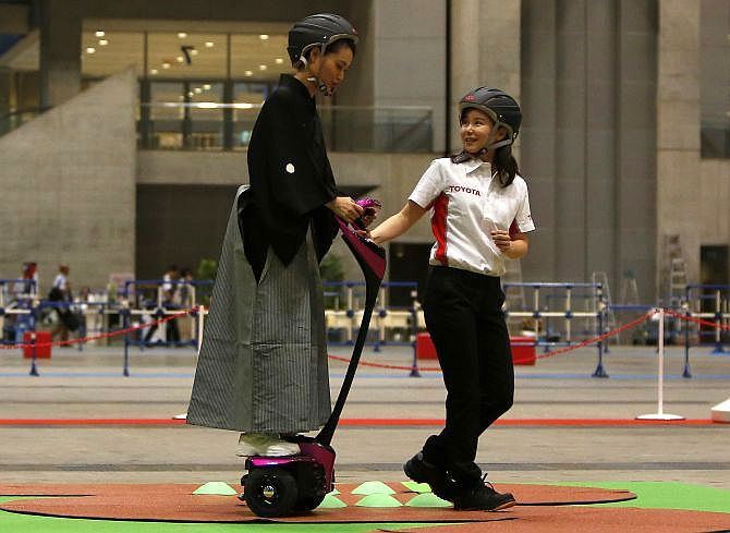 A staff member of Toyota Motor Corp (R) teaches a visitor, wearing Japanese traditional Kimono, how to ride its new personal mobility Winglet.