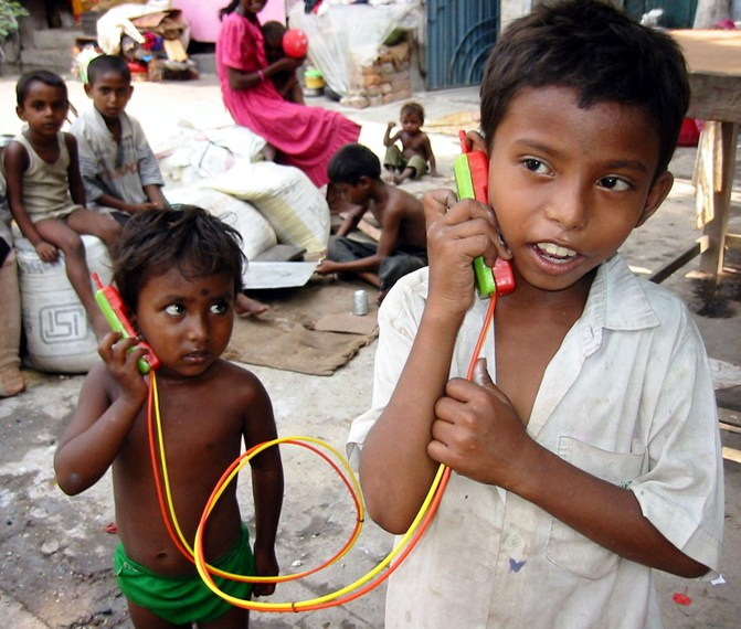 In this file photo, two Indian street children talk to each other through a toy phone in Kolkata.