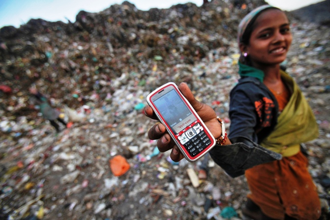 A ragpicker holds her mobile phone to show a picture she took at a dump yard in New Delhi.