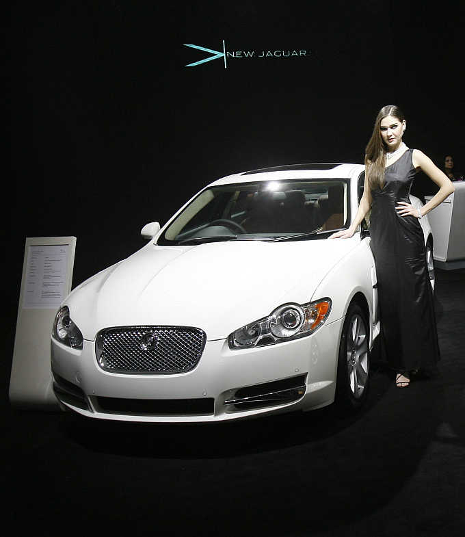 A model poses with a Jaguar XF at India's Auto Expo in New Delhi. Jaguar is a Tata brand.