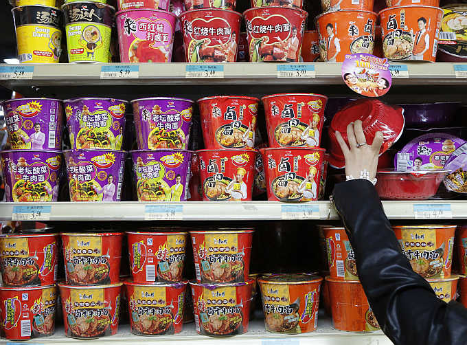 A woman chooses a cup noodle from a shelf at a supermarket in Beijing, China. Photo is for representation purpose only.