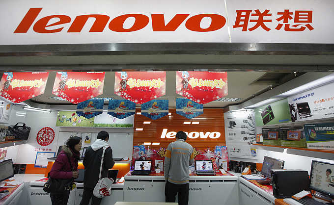 Customers talk to a salesperson at a Lenovo shop in Shanghai, China.