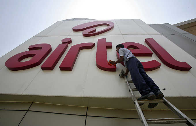 A worker cleans a logo of Bharti Airtel at its zonal office building in Chandigarh.
