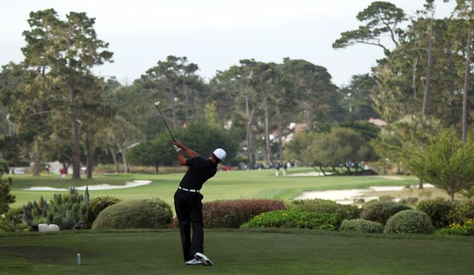Tiger Woods hits his tee shot on the third hole at Monterey Peninsula Country Club.