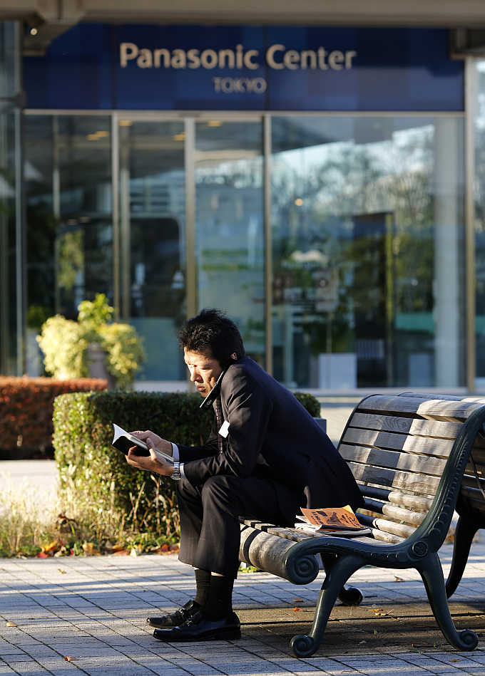 A man uses his mobile phone in front of Panasonic's showroom in Tokyo, Japan.