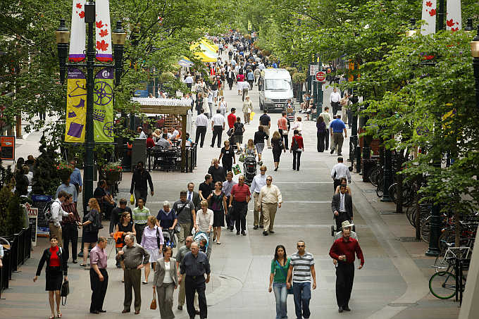 People stroll down the historical Stephen Avenue Walk in the heart of downtown Calgary, Alberta, Canada.
