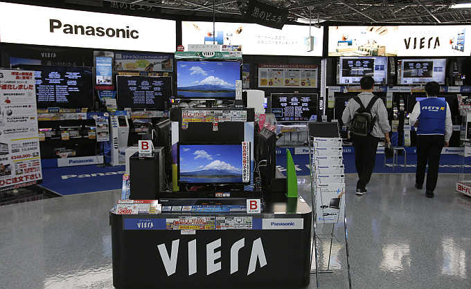 A man walks past Panasonic's Viera televisions displayed at an electronics store in Tokyo, Japan.