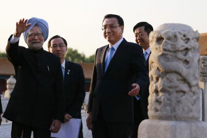 China's Premier Li Keqiang (2nd R) gestures as Prime Minister Manmohan Singh (L) waves during their visit to the Forbidden City, in Beijing, October 23, 2013.