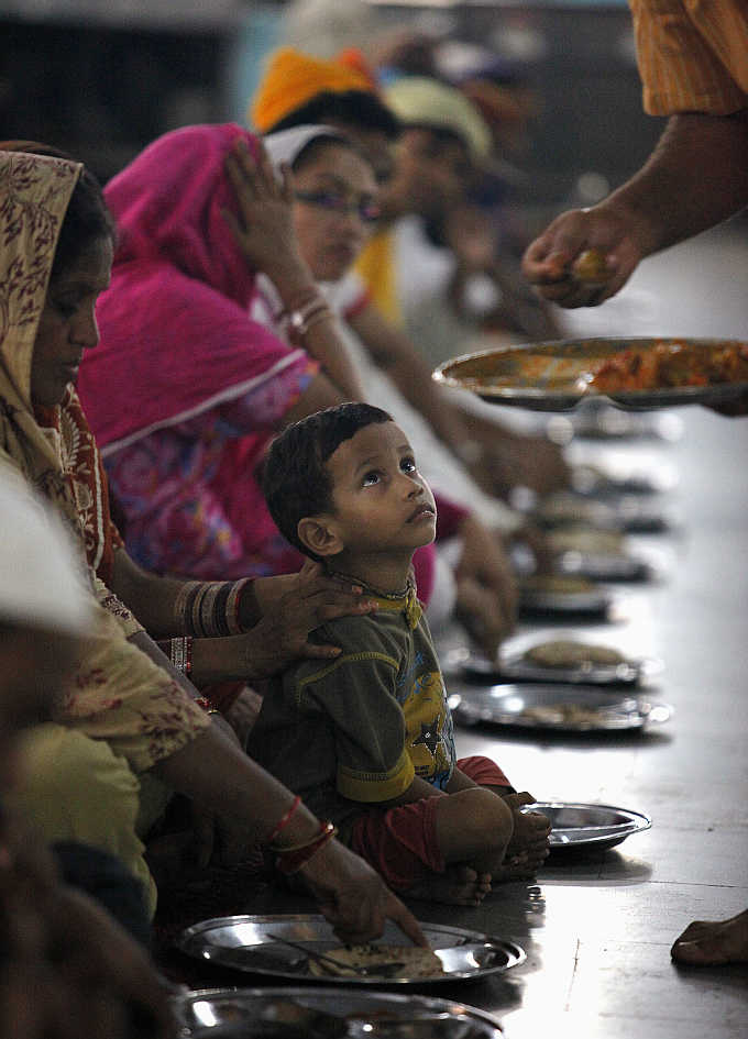 A boy waits for his meal at a community kitchen at a Sikh temple in the old quarters of Delhi.