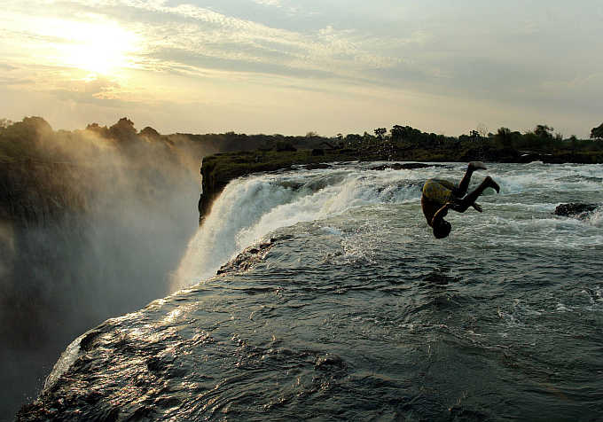 A man somersaults at the edge of the 110 metre high main falls of the Victoria Falls on the Zambezi River which forms the border between Zambia and Zimbabwe.