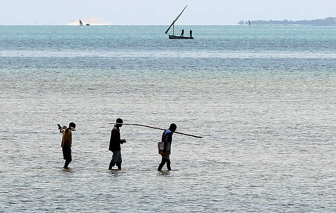 Fishermen walk to a boat on the Indian Ocean shore line in Vilanculo, Mozambique.