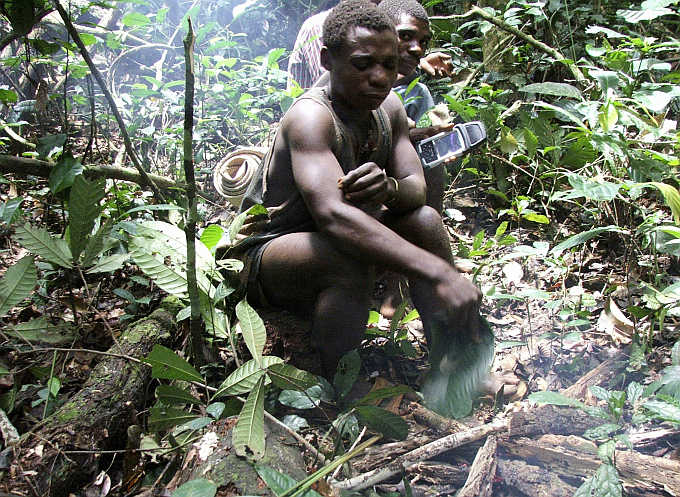 Baka, a Mbendjele pygmy, stops to make a fire in the northern forests of the Congo Republic while another behind him holds a Global Positioning System handset.