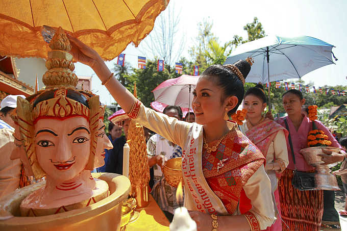 Nang Sangkhan, or Miss Lao New Year, pours water mixed with frangipanis and perfume over the head of a statue as she takes part in Lao New Year celebrations in capital Vientiane.