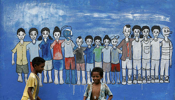 East Timorese children play near a mural in capital Dili.