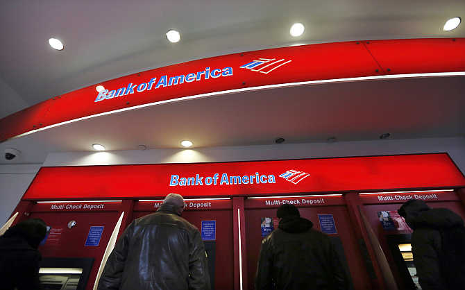 Customers use ATMs at a Bank of America centre in New York City's financial district.
