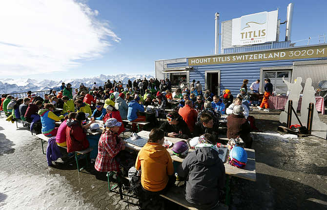 Skiers and tourists sit at a restaurant terrace at the mountain station of the Mount Titlis cablecar (3,020 metres) near the mountain resort of Engelberg, Switzerland.