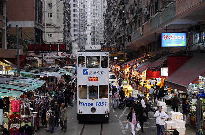 A tram passes by a marketplace in downtown Hong Kong.
