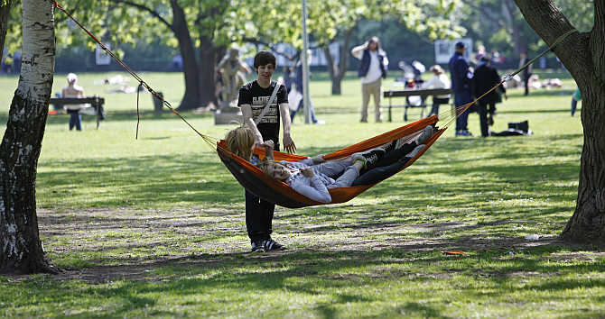 People relax in a hammock on a sunny day in Kampa park in central Prague, the Czech Republic.