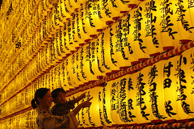 A family looks at paper lanterns during the Mitama Festival at Yasukuni Shrine in Tokyo, Japan.