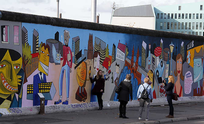 People take pictures of painted artwork of contemporary German Pop artist Jim Avignon at the open air 0.8-mile painted section of the Berlin Wall known as the 'East Side Gallery' in Berlin, Germany.