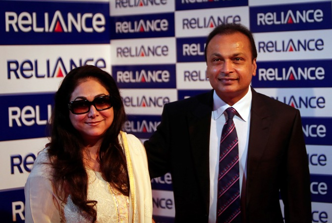 Anil Ambani, chairman of the Reliance Anil Dhirubhai Ambani Group, poses with his wife Tina Ambani for photographers before addressing the annual shareholders meeting in Mumbai August 27, 2013.