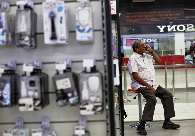 A man speaks on his mobile phone as he sits outside an electronics store in New Delhi.