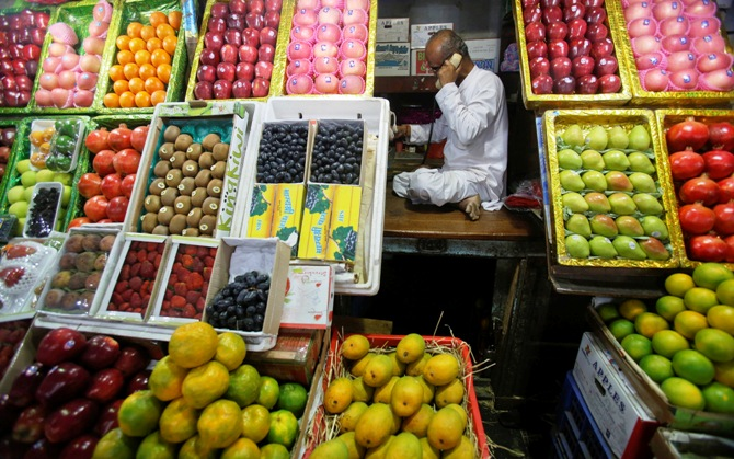 A fruit vendor speaks on his phone while sitting at his fruit stall at a wholesale market in Mumbai.