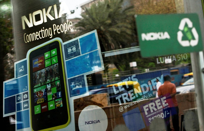 A man is reflected on the glass door of a Nokia showroom in New Delhi.