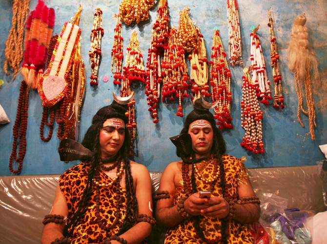 Artists dressed as the Hindu Lord Shiva read a message on a mobile phone as they prepare to participate in a religious procession ahead of the Mahashivratri festival in Jammu.