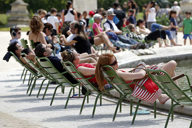 People relax in chairs around a fountain as they take in the sun in the Tuileries Garden in central Paris, France.