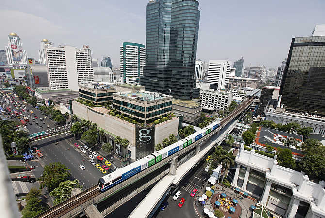 A skytrain passes over vehicles on road in Bangkok, Thailand.