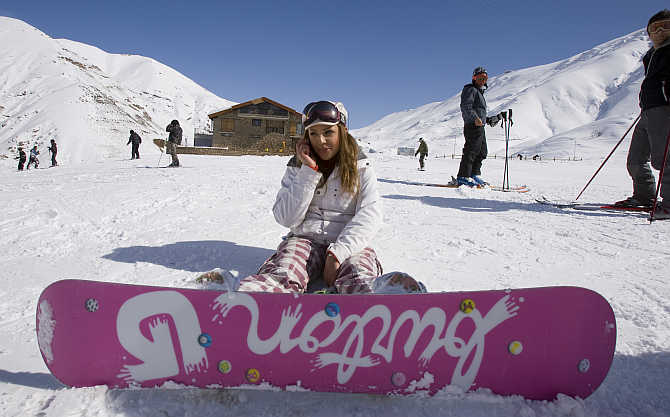A woman speaks on her mobile phone at the midway point of a slope at Shemshak ski resort, 30km north of Tehran, Iran.
