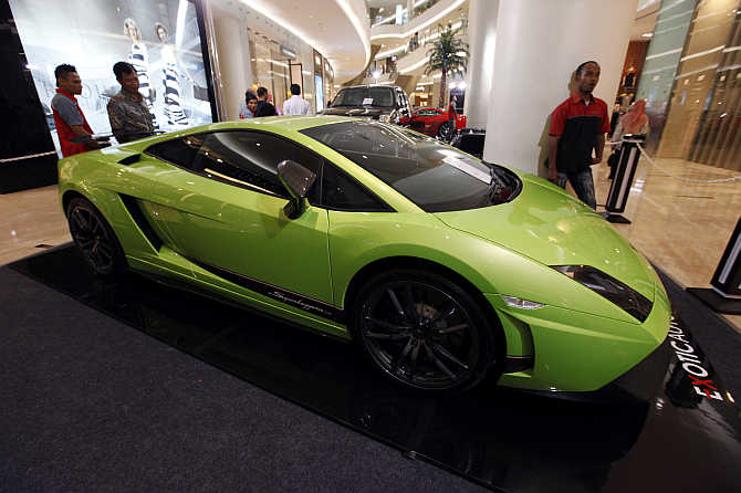 Men look at a Lamborghini on display at a shopping mall in Jakarta, Indonesia.
