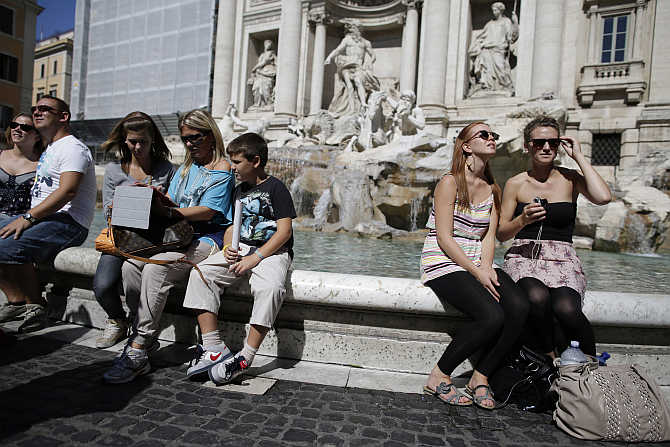 Tourists sit in front of Trevi Fountain in Rome, Italy.
