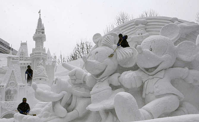 Soldiers clear snow on a sculpture celebrating the 25th anniversary of the Tokyo Disney Resort at a festival in Sapporo, northern Japan.
