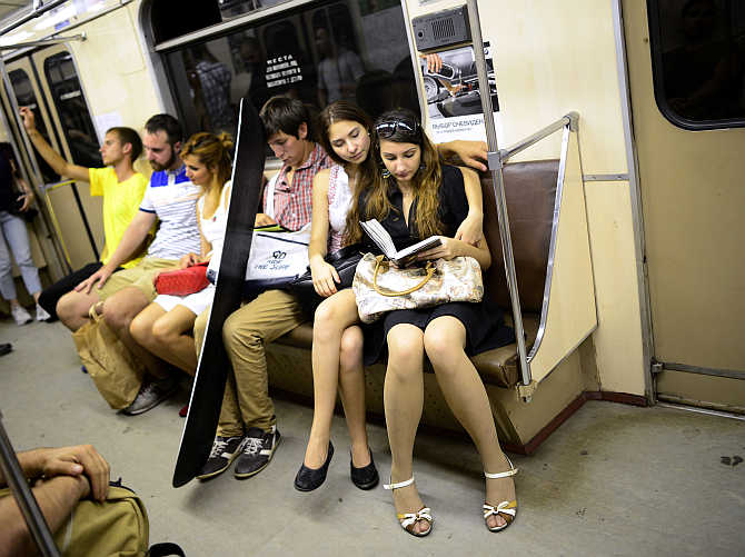Two women read a book as they sit in a train on the metro in Moscow, Russia.