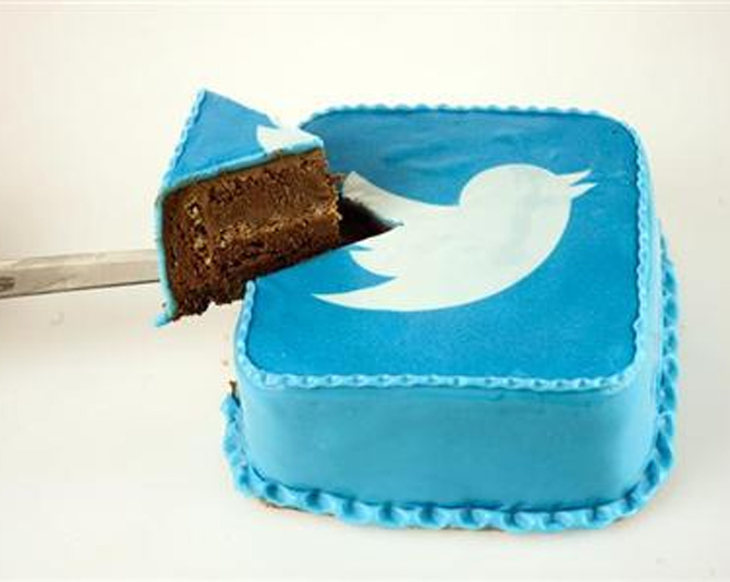A person takes a slice of cake which is decorated in blue icing sugar with a Twitter logo at a bakery in Skopje.