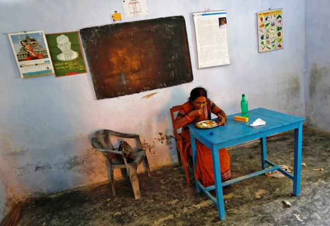 Srimati Kumari, a school headmistress, eats the free mid-day meal, distributed by a government-run primary school, before being served to schoolchildren at Brahimpur village in Chapra district of Bihar.