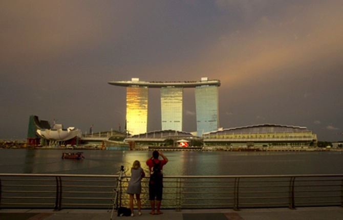 Tourists stand at a promenade across the water from the Marina Bay Sands integrated resort in Singapore.