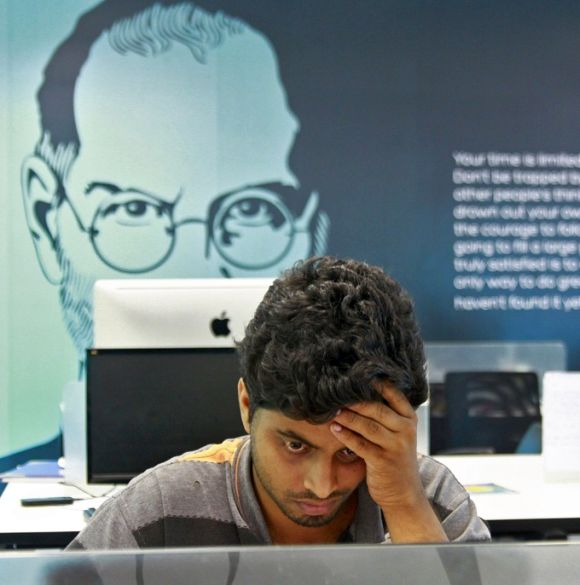 An employee works on a computer terminal against the backdrop of a picture of late Apple co-founder Steve Jobs.