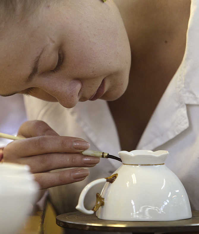 An employee paints a cup at a porcelain factory in the town of Dobrush, about 350km southeast of Minsk, Ukraine.