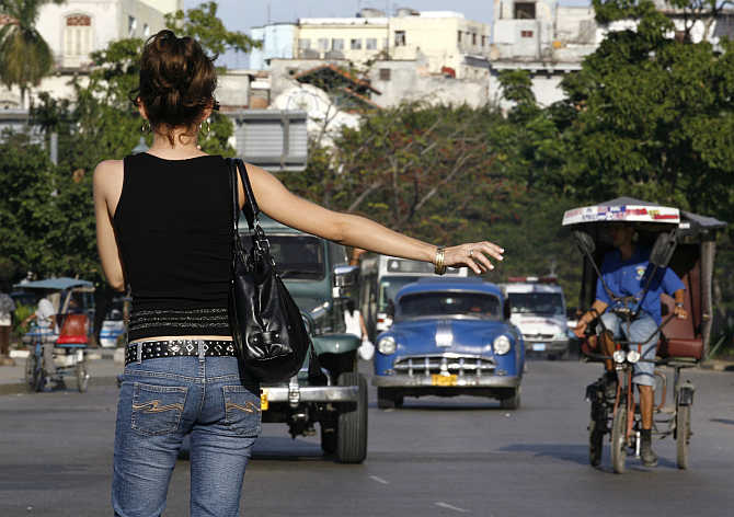 A woman hails a vintage car used as a taxi in Havana, Cuba.