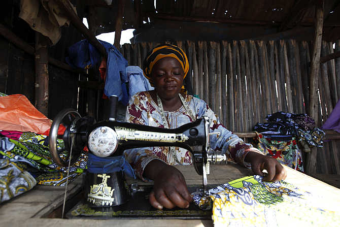A woman sews clothes on a sewing machine in Gatumba, outside Bujumbura, Burundi.